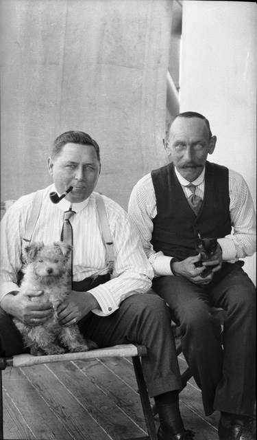 Two crew members holding pet dog and cat. Image: Samuel Hood / ANMM Collection 00023639.