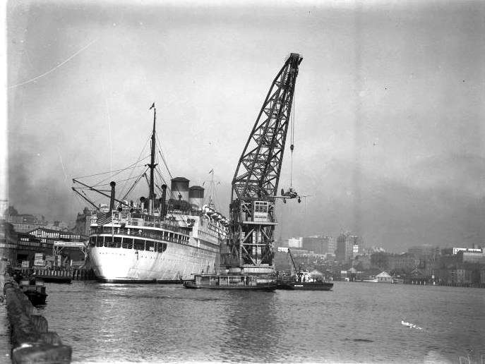Wartime: SS Mariposa in Sydney, unloading an aircraft. ANMM Collection 00035944.