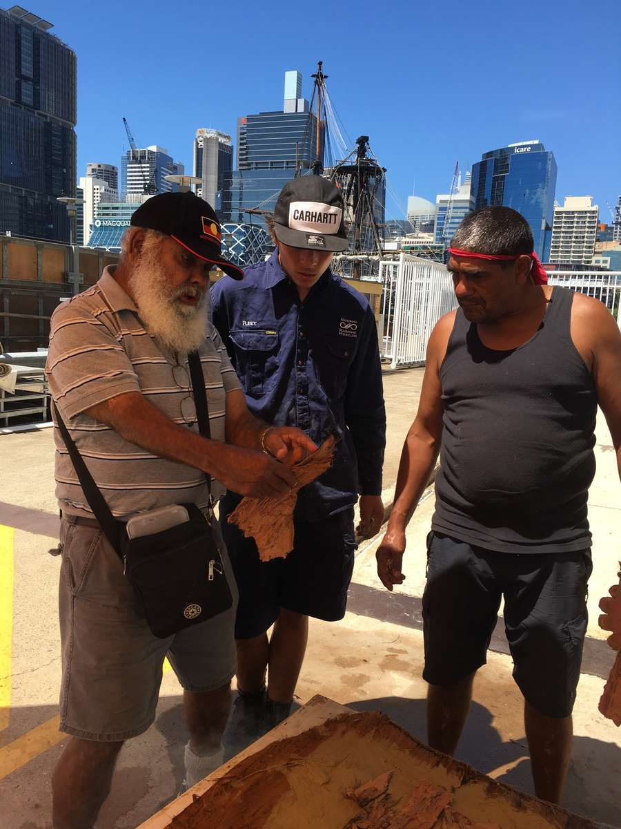 Uncle Max, Dean and Riley Hughes Indigenous apprentice with the museum discuss the bark. Image: Donna Carstens /ANMM.