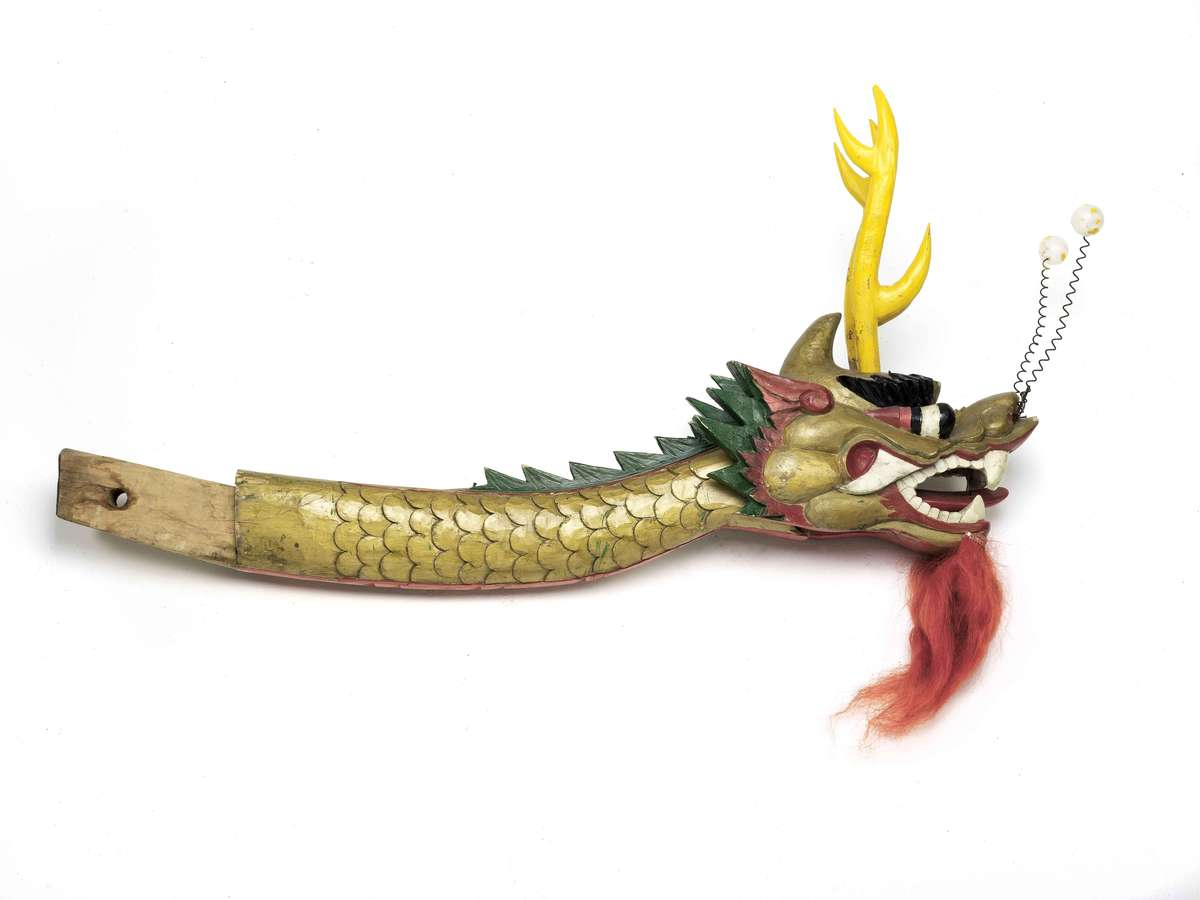Dragon boat figurehead painted gold, green and beige with red beard and white plastic antennae. ANMM Collection 00039729, Gift from Carlos Ung.
