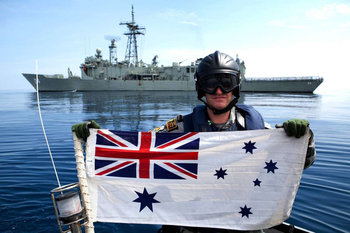 Petty Officer Boatswain Antony Kirk holding the Australian White Ensign during Exercise Bersama Lima, off Western Australia. Photographer ABIS Evan Murphy. Courtesy RAN Imagery Unit.