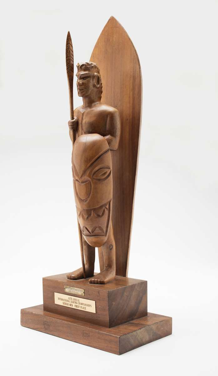 Makaha trophy, 1962, maker unknown, timber, seed and carved timber offerings. Regarded as the unofficial world title, it was won by Bernard 'Midget' Farrelly on 2 January 1963. Gift from Bev Farrelly and family in memory of Bernard 'Midget' Farrelly. ANMM Collection 00054957.
