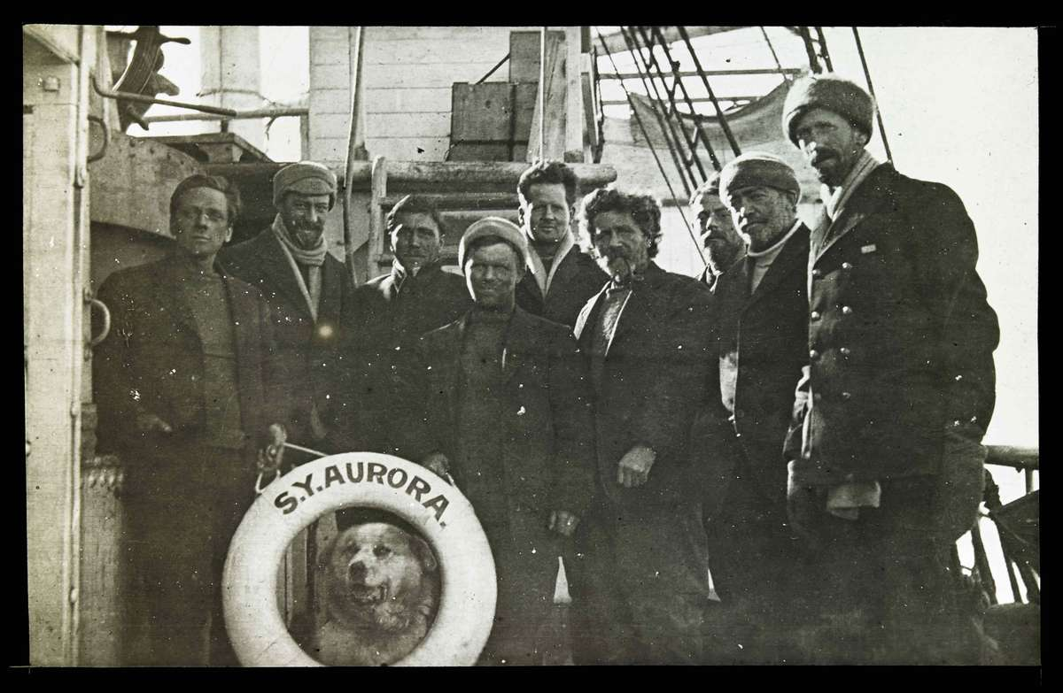 Rescued party of the seven survivors of the Ross Sea Party on Aurora with their mascot Oscar. Sir Ernest Shackleton and Captain John King Davis on the right, January 1917, photographer Frederick Middleton, courtesy the Middleton family, State Library of Victoria