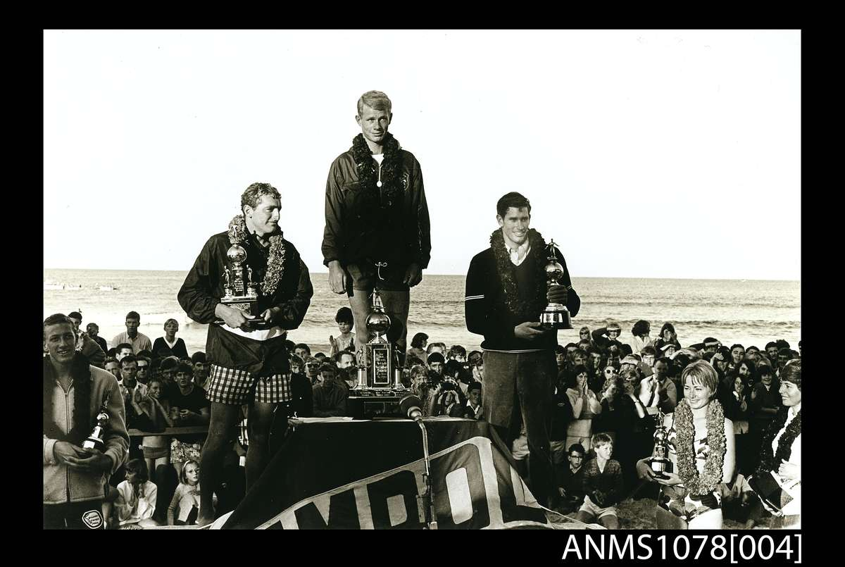 Jack Eden, Presentation of the trophies in the first world open surfboard championships Manly, 1964. Gelatin silver photograph, printed 1990s. Senior men's championship winners on the podium: 1 Midget Farrelly, Australia (centre), 2 Mike Doyle, California (left), 3 Joey Cabell, Hawaii (right). The women's championship winners are on the right: 1 Australian Phyllis O'Donnell (far right) and 2 Linda Benson California (right), with Nat Young, the runner-up in the junior men's final, on the left. ANMM Collection ANMS1078[004], ANMM Collection Gift from Jack and Dawn Eden.