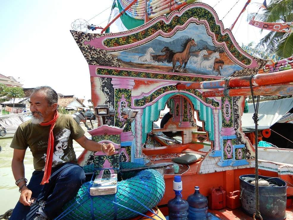 Our Javanese tour director Narto has climbed on board for a closer look at this decorated helmsman's shelter on a Madurese perahu pursen fishing boat.