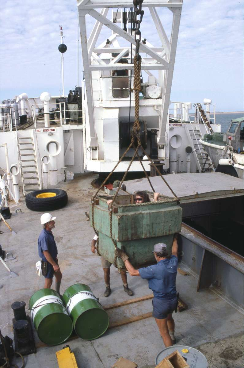 Museum staff member being lifted off the deck of MV Cape Moreton 1987 onto a LARC (amphibious cargo vehicle). All the materials and equipment for the dismantle were transported from the tender to the site using LARCs. Credit: Mike Lorimer.