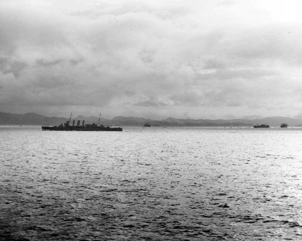 HMAS <em>Canberra</em> underway off Tulagi, during the landings there, 7-8 August 1942, the day before the battle. Three transports are among the ships visible in the distance, with Tulagi and Florida Islands beyond. Image: US Navy History and Heritage Command.