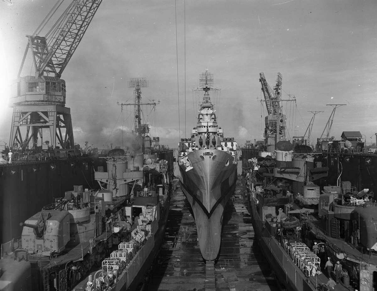 USS <em>Canberra</em> (centre) in dry dock for repairs in December 1944. Image: US National Archive.
