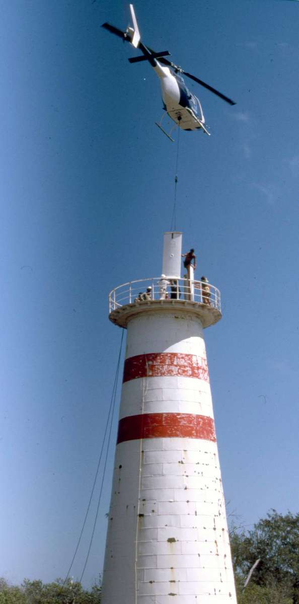 Department of Transport lighthouse service helicopter being used to lift the cast iron walls of the lantern room, 1987. Credit: Michael Pitcher.