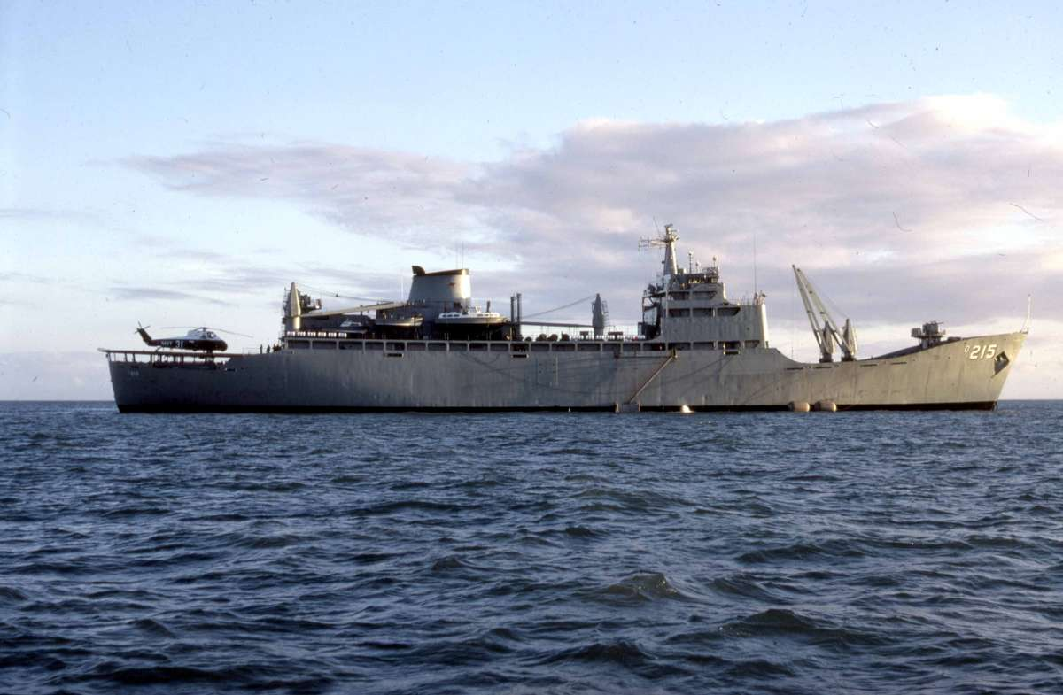 RAN escort maintenance ship HMAS Stalwart and helicopter sitting off Cape Bowling Green ready to receive the dismantled lighthouse and transport it to Sydney, 1987. Credit: Michael Pitcher.