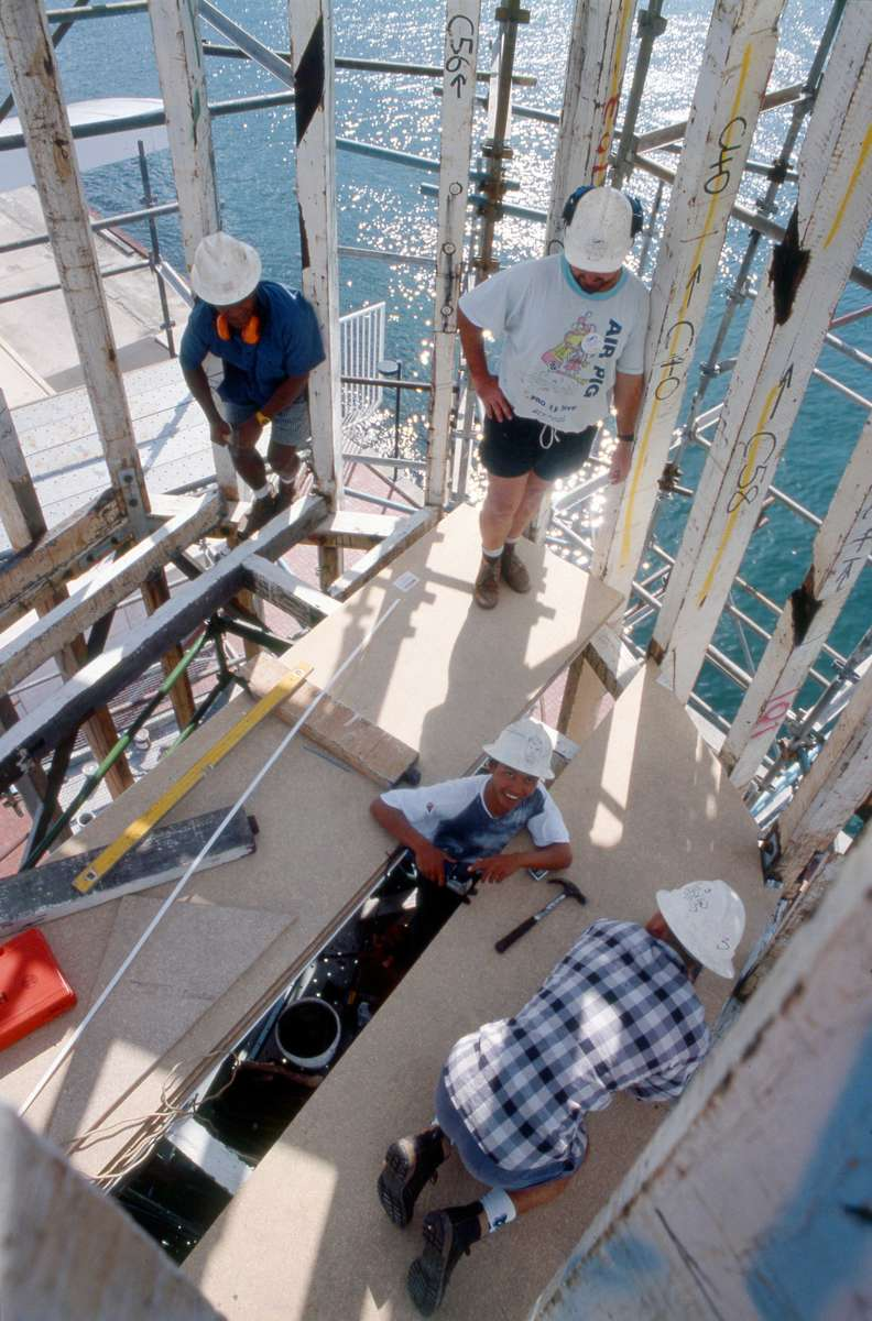 Working high above the harbour, inside the timber structure of the lighthouse, 1994. Image: ANMM.