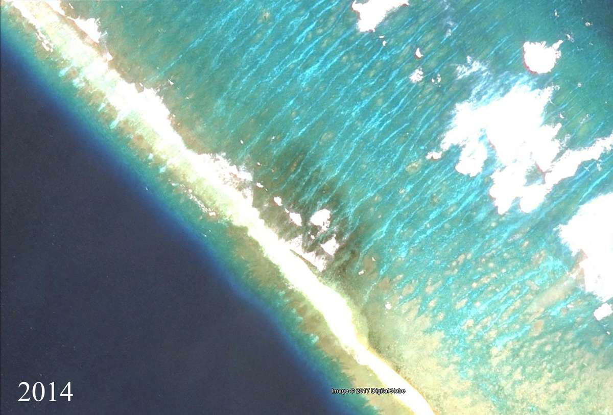 Satellite image of the same section of Kingman Reef in 2014, showing the proliferation of 'black reefs' around the wrecked vessel (which is no longer visible above the water's surface). Image: Google Earth/DigitalGlobe/NOAA.
