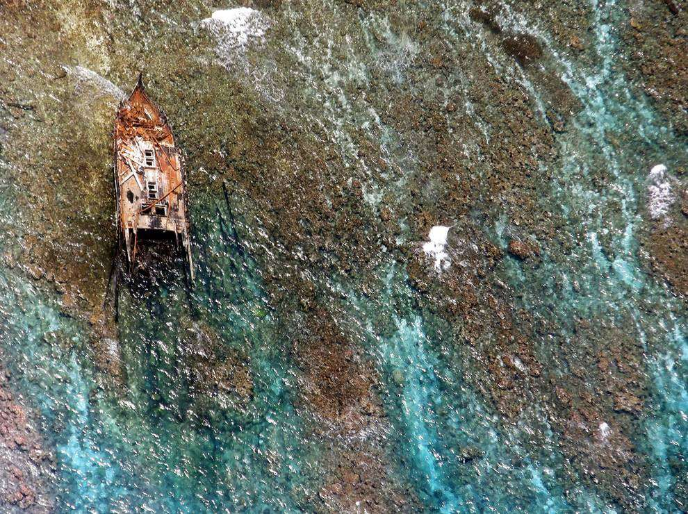 Close-up image of the wrecked vessel at Kingman Reef, showing areas of adjacent reef colonised by dark green algae. Image: Jim Maragos/US Fish and Wildlife Service. Source: NOAA.