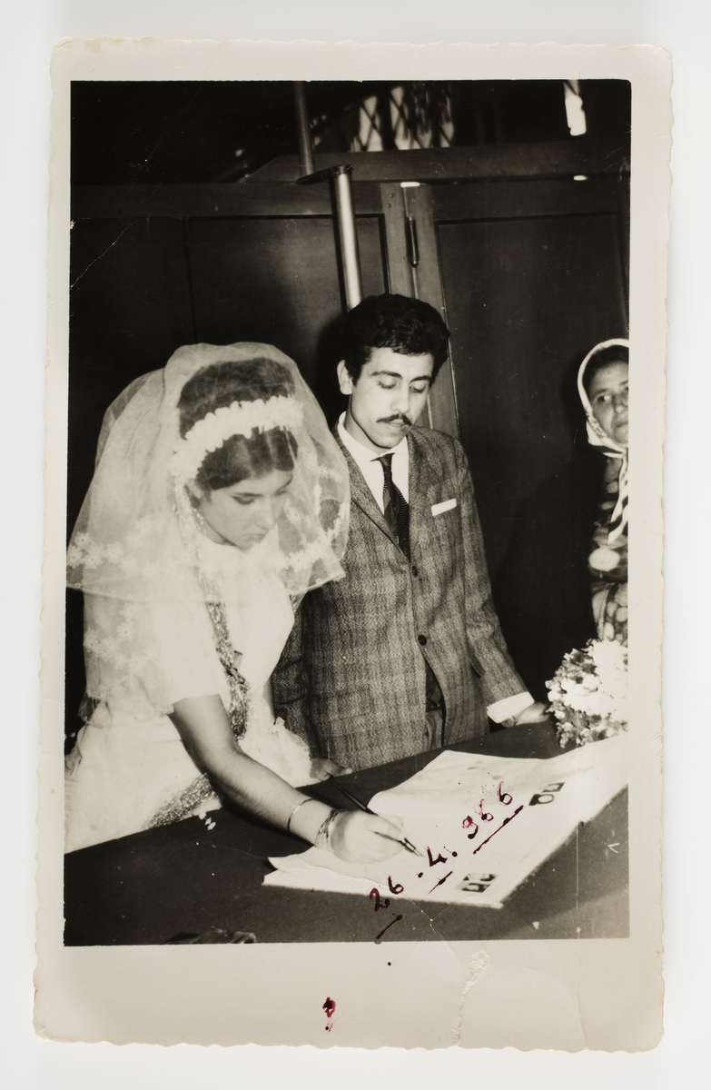 Şükran and Halit Adasal signing their marriage documents, with Şükran's mother Sultan Salman at far right, Adana, Turkey, 1966. Reproduced courtesy Hale Adasal