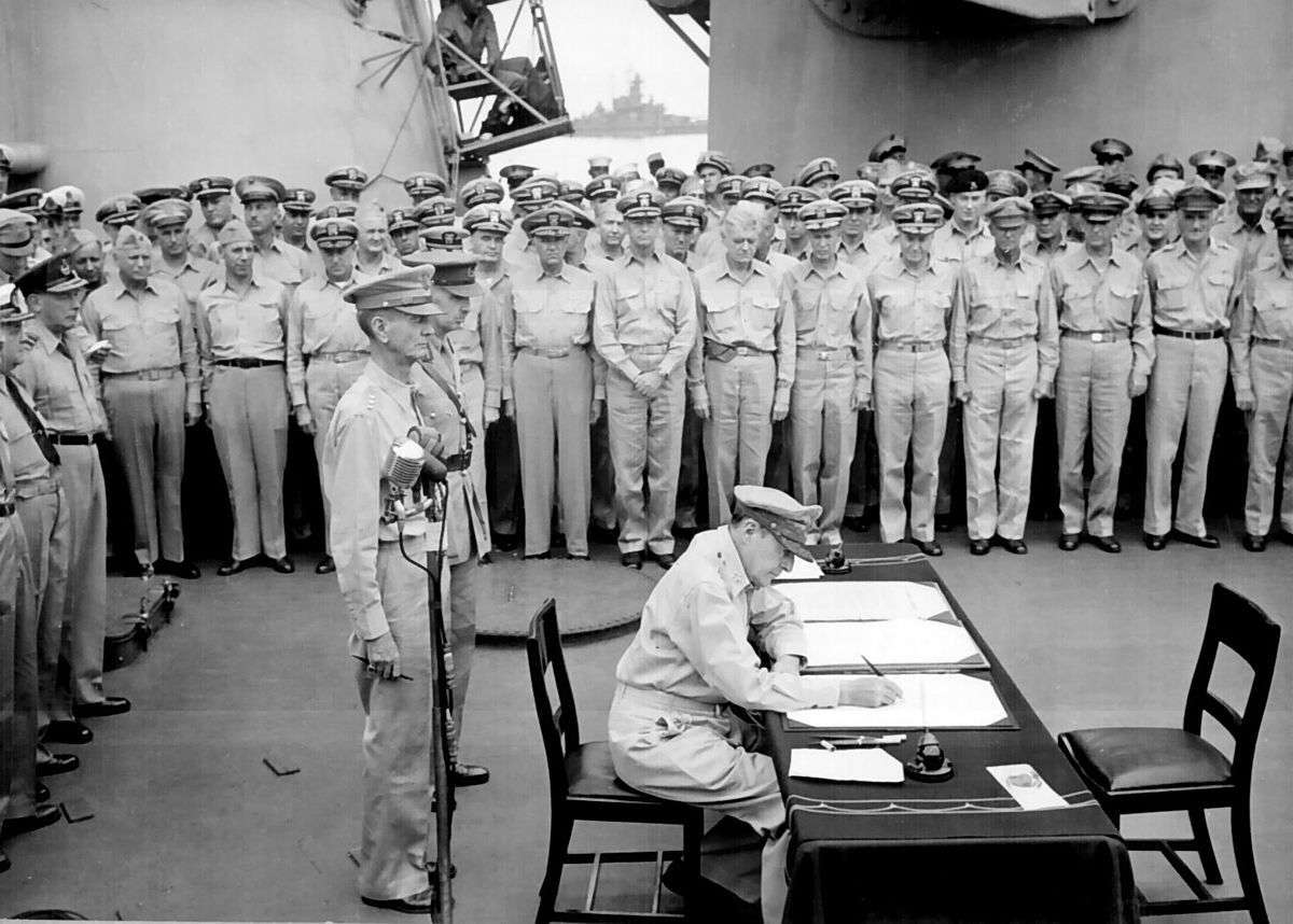 General Douglas MacArthur signs as Supreme Allied Commander during formal surrender ceremonies on the USS MISSOURI in Tokyo Bay. Image: Naval History and Heritage Command.