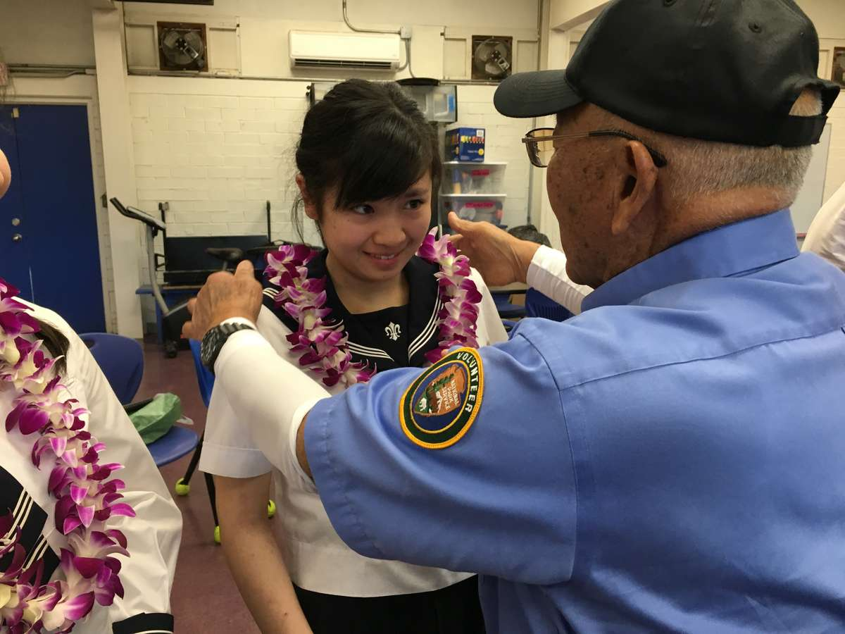 Jimmy Lee presenting Saki with a welcoming lei. Image: ANMM.