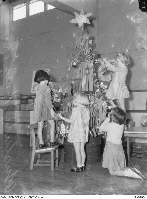 "Four little girls decorate their austerity Christmas tree at a suburban school. The tree branches are constructed of sticks hung with fringed paper and foil stars are used as decorations.<a href=""https://www.awm.gov.au/collection/136997"">AWM Collection</a>."