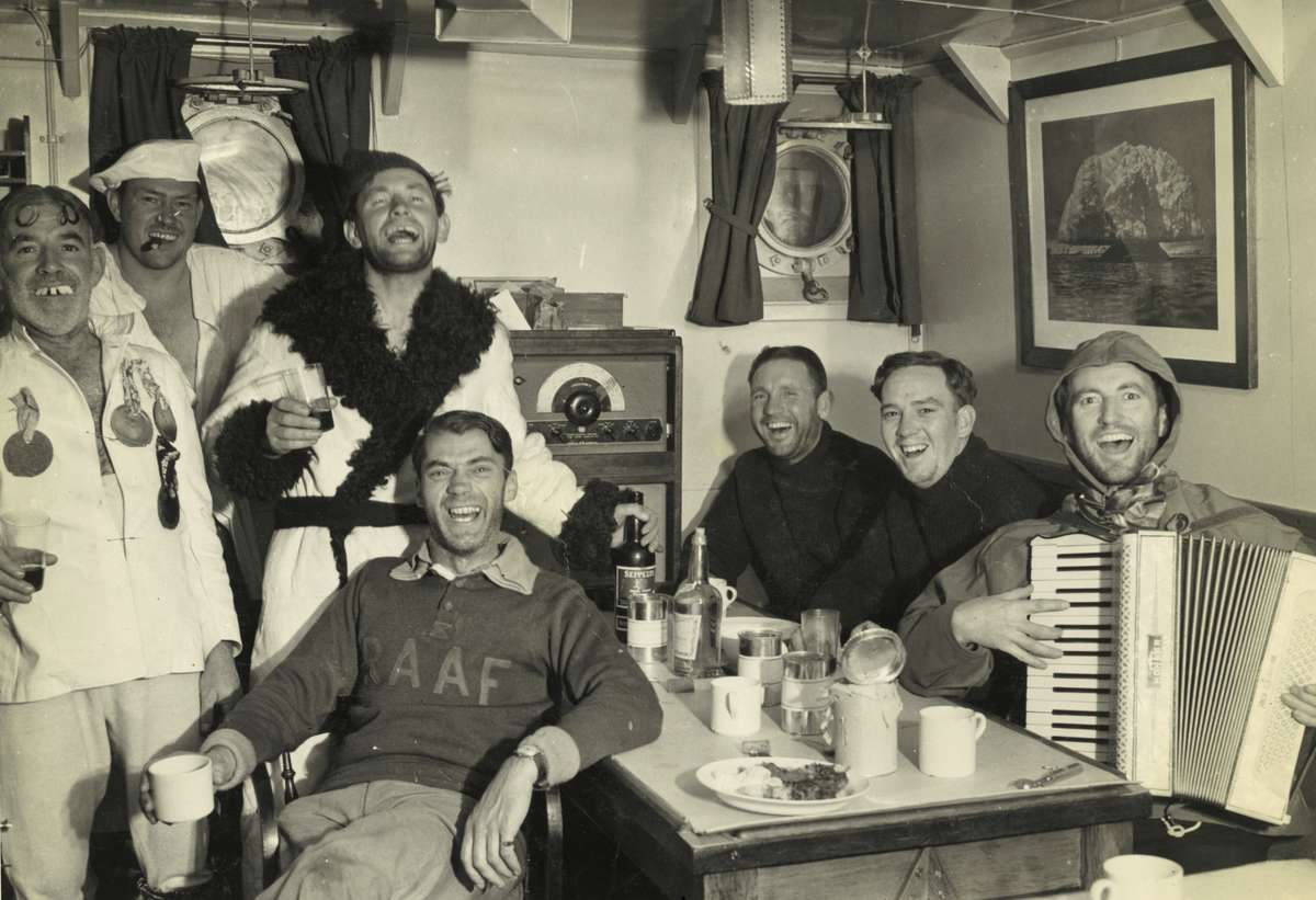 Wyatt Earp officers and ANARE scientists celebrate during an 'Across the Circle' party, February 1948. Left to right: LCDR Harold Irwin (engineer officer), Dr A Bond (medical officer), LCDR William Cook, RAAF Squadron Leader R H Gray (Kingfisher pilot), ASCB John Homewood (boatswain), LT John Yule (watch keeper), and Phillip Law (chief scientific officer). ANMM Collection ANMS1445[127].