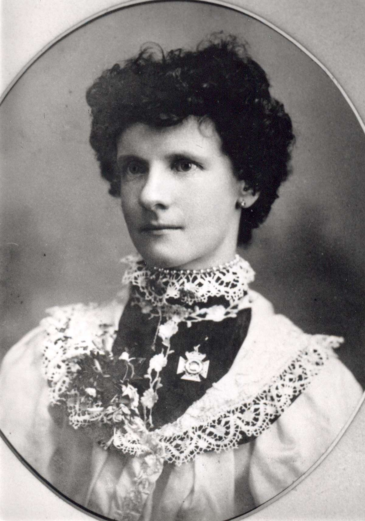 Irene Pritchard wearing her Anniversary Day medal. The top of the medal, which is in the shape of a Maltese cross, is a yacht. Photo courtesy Nedlands Library, WA