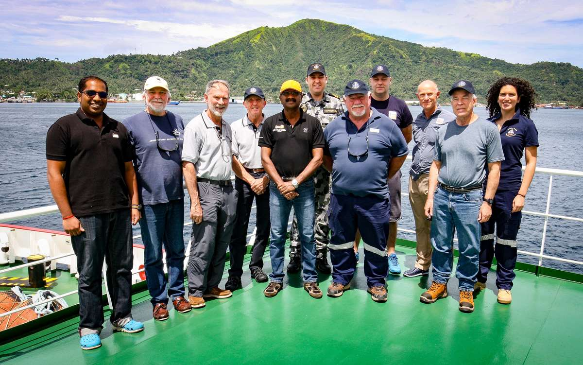 Members of the Find <em>AE1</em> expedition team with representatives from Fugro Survey in Simpson Harbour, Rabaul, Papua New Guinea. From left: Tanesh Thanapalan (Fugro Survey), Paul Hundley (Silentworld Foundation), Rear Admiral Peter Briggs AO CSC RAN(Rtd) (Find AE1 Ltd), Captain Roger Turner RN Rtd (Find AE1 Ltd), Chandran Karapiah (Fugro Survey), Lieutenant James McPherson RANR (Royal Australian Navy), Gus Mellon (Find AE1 Ltd), Andrej Masloboev (Fugro Survey), Magnus Windle (Fugro Survey), Nigel Erskine (Australian National Maritime Museum), Irini Malliaros (Silentworld Foundation). Image: Bayden Findlay/ Find the Men of <em>AE1</em> Ltd.