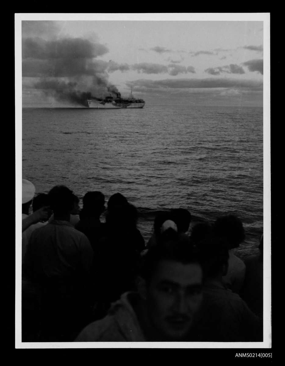 Passengers watch from the deck of City of Sydney as Skaubryn burns in the Indian Ocean, 1958. ANMM Collection Gift from Barbara Alysen ANMS0214[005]. Reproduced courtesy International Organisation for Migration.