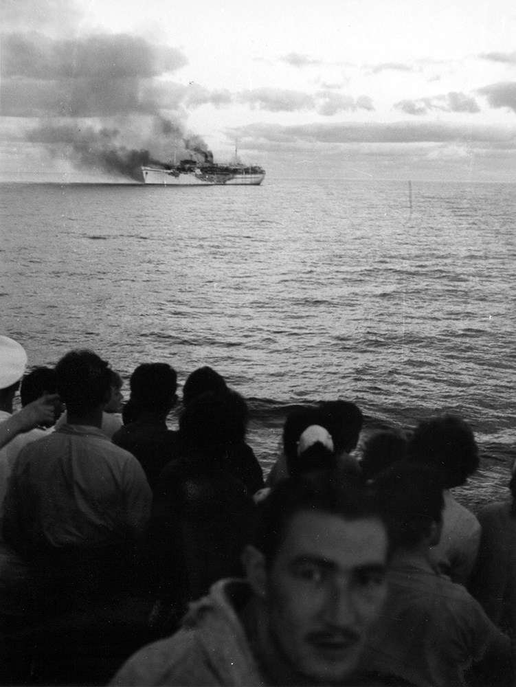 Passengers watch from the deck of <em>City of Sydney</em> as <em>Skaubryn</em> burns in the Indian Ocean, 1958. ANMM Collection Gift from Barbara Alysen ANMS0214[005]. Reproduced courtesy International Organisation for Migration.