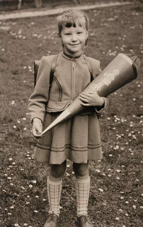 Five-year-old Ute Gabriel on her first day of school, West Germany, 1955. Ute carries a traditional German Schultüte (school cone), a gift from her parents containing pencils, notebooks, rulers and sweets. Reproduced courtesy Ute Mahoney.