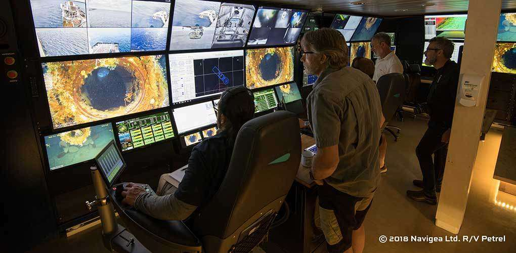 Maritime archaeologists and technicians study the shipboard computer screens during the 3D photographic survey of submarine HMAS <em>AE1</em>, in early 2018. Image courtesy Navigea Ltd.