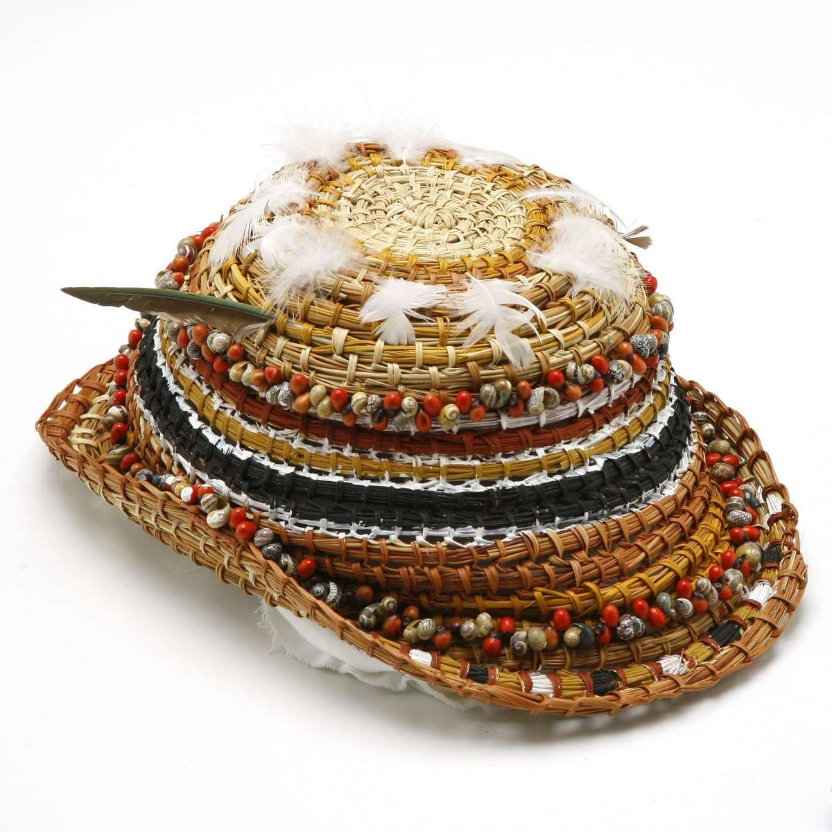 Hat woven from natural fibres with strings of small shells, seeds and feathers with painted decoration. ANMM Collection 00040541.