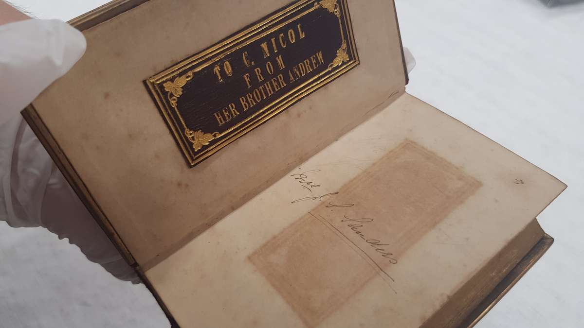 The leather and gilt label on the frontpage has stained the opposite page. ANMM Collection00054909.