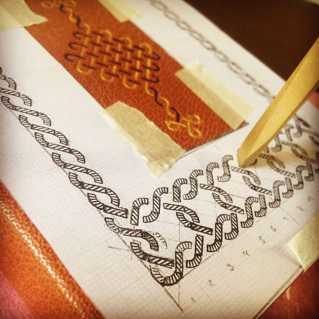 Hand stamping decorations on to leather cover and using lapis lazuli and gold pigments to add colour. Image: Lucilla Ronai.