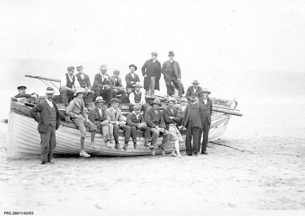 Men and boys who were part of the rescue party for survivors of the wrecked steamer Clan Ranald standing with their lifeboat at Troubridge Hill beach near Edithburgh, South Australia. Courtesy State Library of South Australia.