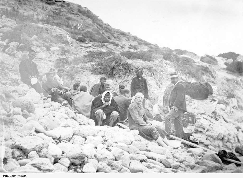 Shocked survivors from the wrecked ship Clan Ranald sitting amongst rocks at Troubridge Hill on the Yorke Peninsula. Some are wrapped in blankets and a policeman stands with them. Courtesy State Library of South Australia.