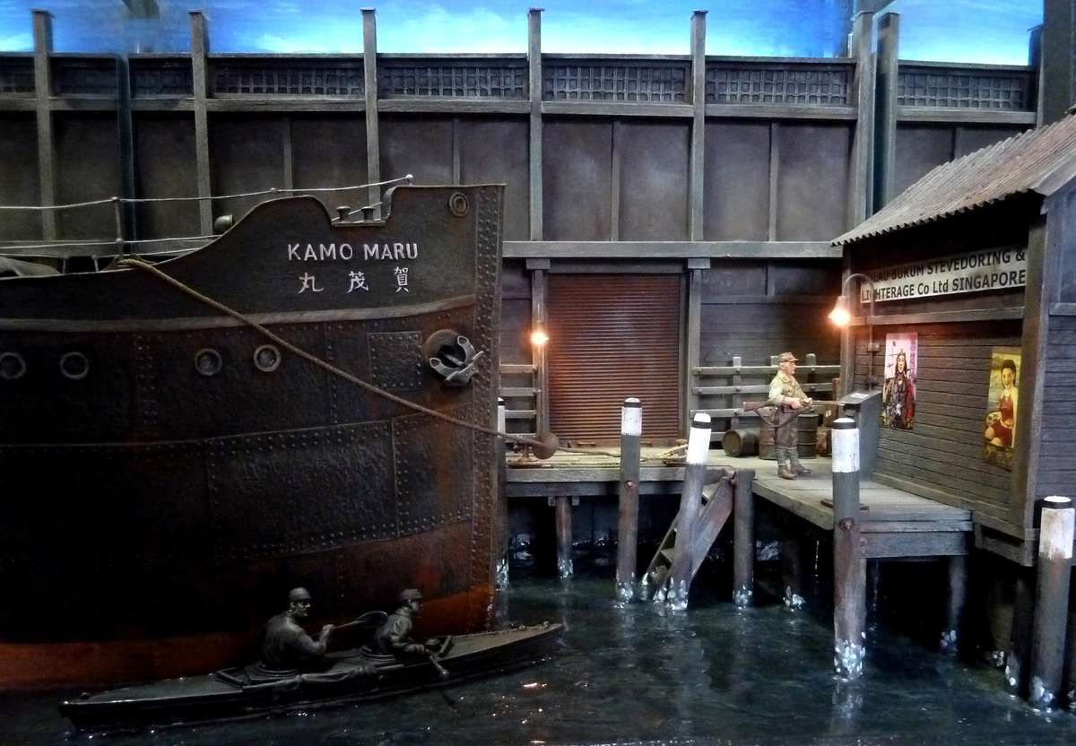 A smaller diorama features Lieutenant Page and Able Seaman Jones in Canoe No.3 at Pulau Bukum docks, Singapore. Dimensions 53cm wide by 32cm deep by 65cm high. Dockland background built into diorama. Low-level cold lighting. Image: Geoff Barnes.
