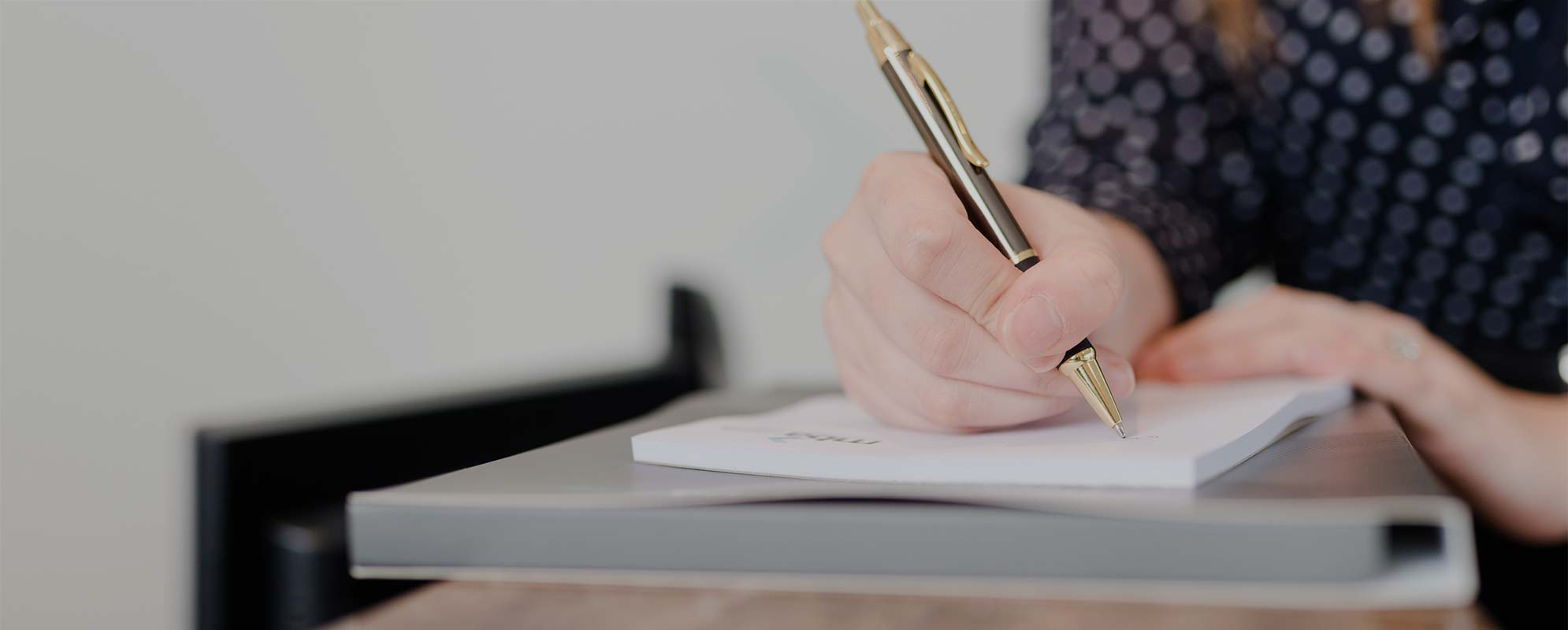 Woman Holding Pen Writing on Paper