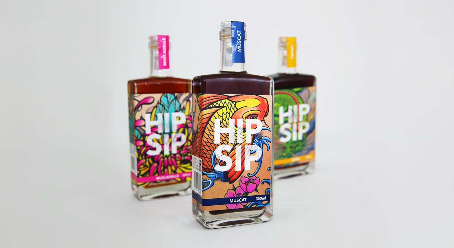 Trio of Hip Sip bottles with tattoo artwork on grey background