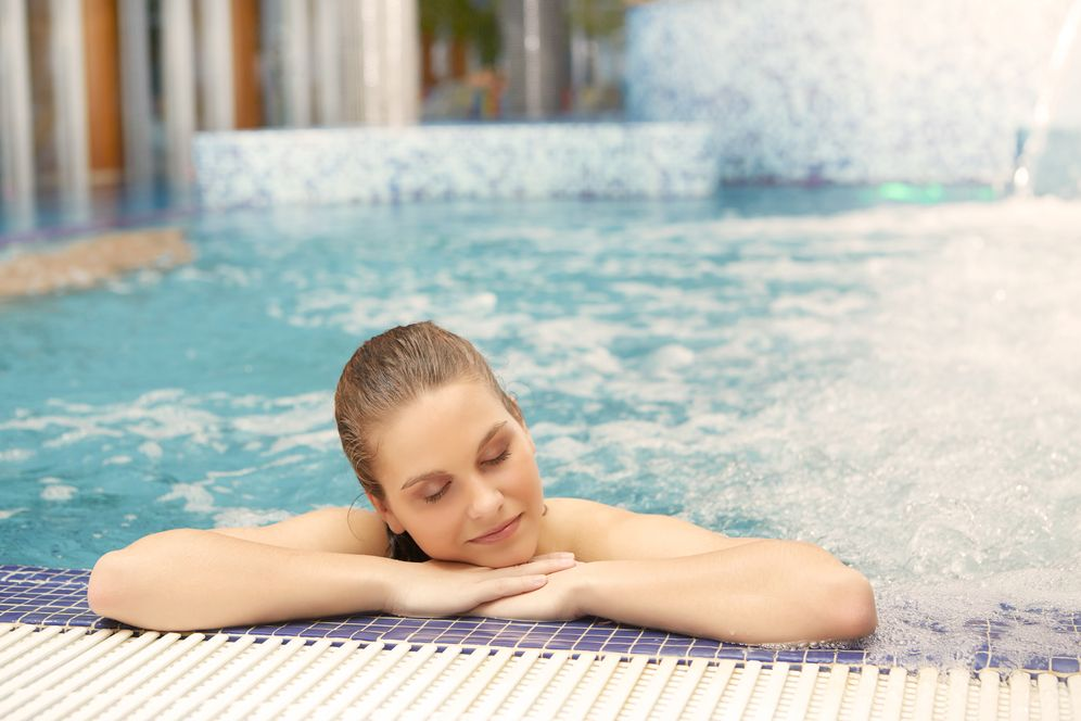 A woman relaxing in a steamy heated pool