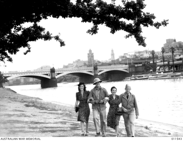 Two American servicemen are strolling arm-in-arm with Australian girls along the banks of the Yarra. 011543.