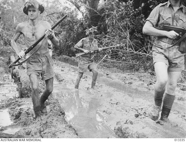 1942-10-01. NEW GUINEA. MILNE BAY. AUSTRALIAN TROOPS PLOUGH THROUGH THE MUD AT MILNE BAY SHORTLY AFTER THE UNSUCCESSFUL JAPANESE INVASION ATTEMPT.