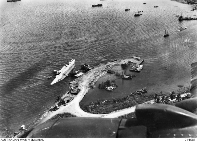 Gili Gili wharf at Milne Bay in April 1943, showing the freighter Anshun still lying capsized in the shallows where she was sunk by Japanese warships on 6 September 1942