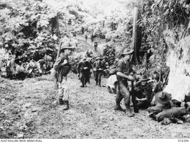 Men of the 29th/46th Battalion have a short spell after plodding up a steep, muddy road north of Gusika, AWM 016294