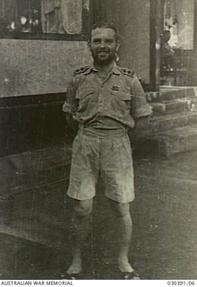 Informal portrait of Lieutenant (Lt) Mullens, 2/2nd Australian Pioneer Battalion, in the Officers' Compound, Bicycle Camp. Lt Mullens has just returned to the camp after being subjected to torture ..