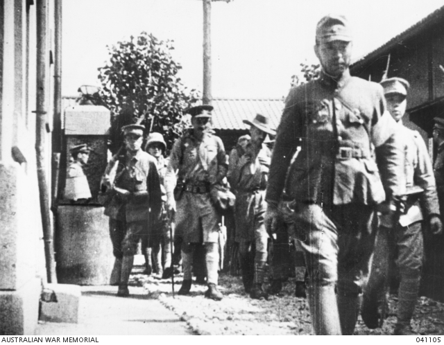 Japanese Lieutenant Tarada followed by British officers entering the prisoner of war camp.