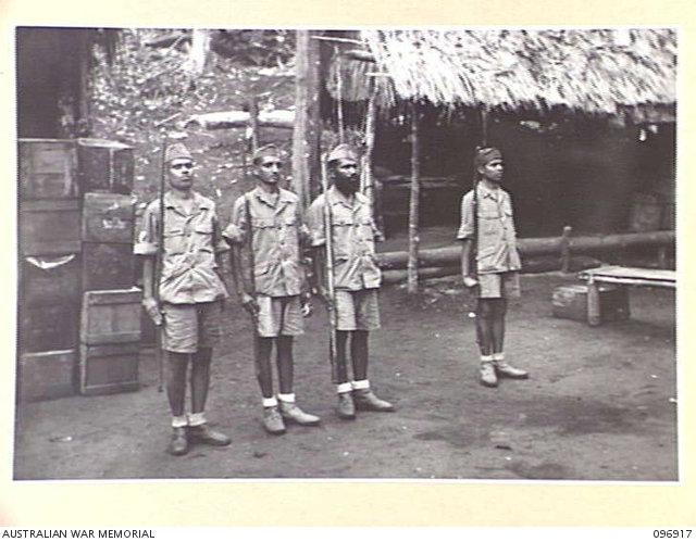 Indians mount guard with sticks at Kumuia Yama, New Britain, within days of being recovered in September 1945.