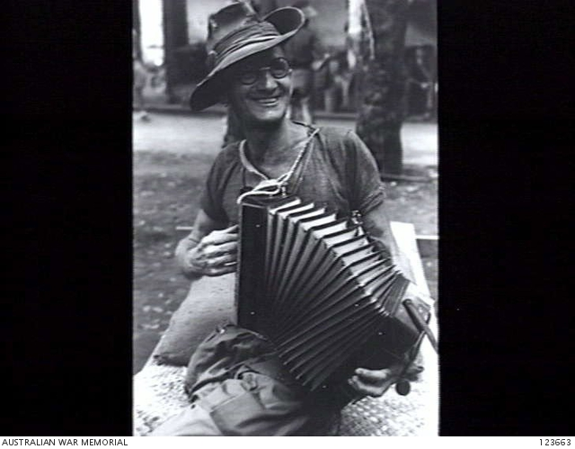 An unidentified Australian ex prisoner of war playing his accordion at Bicycle Camp