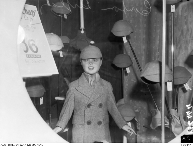 A window display showing the price tag and number of coupons required for the purchase of a child's overcoat and caps