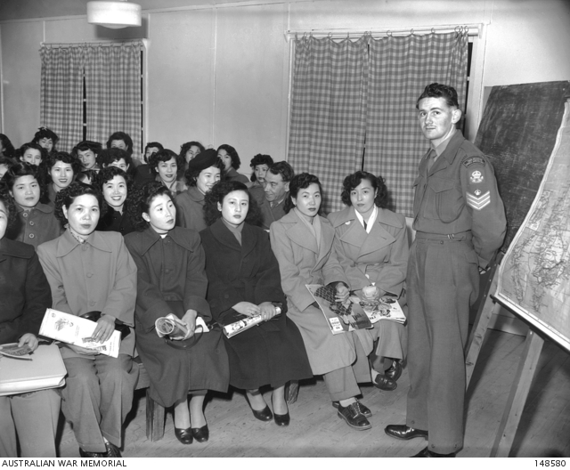 Kure, Japan. c.1952. 3/3522 Sergeant T. R. MacQuin of Australian Army Education Service stands in front of a class of Japanese war brides to give them information about Australia. 148580.