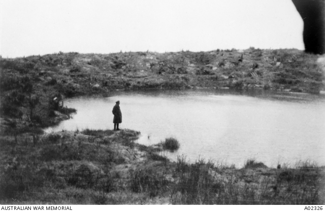 Wytschaete crater.  A soldier standing next to a water filled mine crater near Wytschaete, which was blown up by Australian Engineers at the commencement of the Battle of Messines .