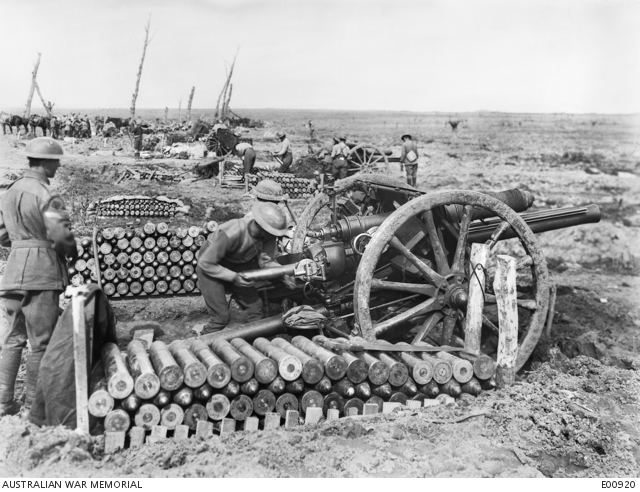 The 14th Battery of Australian Field Artillery in action near Bellewaarde Lake, in the Ypres Sector. Alongside this position was the famous 'Corduroy', a track, the only one possible, used by all troops moving forward. Completely encircling Bellewaarde Lake, it was continuously under shellfire, and many casualties were sustained by the Australians in its vicinity. Identified, left to right, foreground: Corporal Nixon; Gnr (Gnr) Fosberg, placing shell in gun (died of wounds a few days after this photograph was taken. Unable to verify this name on the First World War Nominal Roll); 29349 Gnr T C Roberts (partially obscured); 7090 Sergeant Richard, fitter (extreme right with back to camera); 28314 Gnr J M Bruton (in background, in line with rows of shells, wearing shorts).