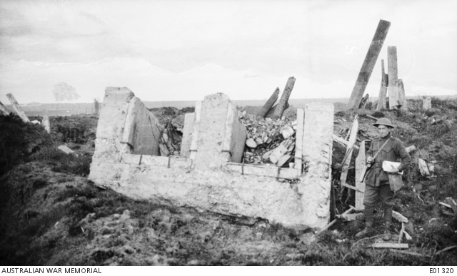 A German pillbox which was overturned by the explosion of a mine, opposite the front, on the early morning of 7 June, just prior to the attack which opened the Battle of Messines. The soldier on the right, carrying what appears to be the Kodak Pocket Camera case over his left shoulder, is 2585 Corporal Ernest Lionel Bailey, 51st Battalion and Australian Corps Salvage AIF, who was accidentally killed in France on 17 May 1918 while gathering exhibits for the Australian War Records Section.